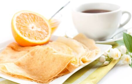 pancakes topped with orange juice and tea, close-up