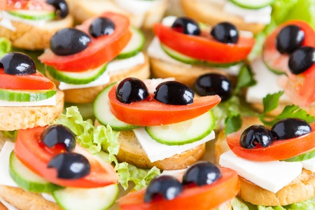 sandwiches with soft cheese and olives, close-up photo