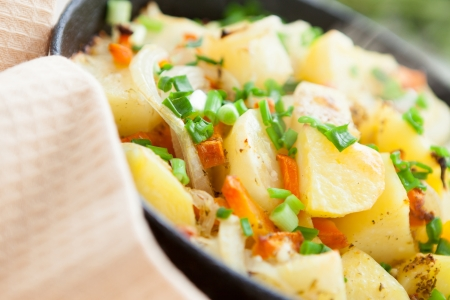 large chunks of potatoes with vegetables and cheese, close-up