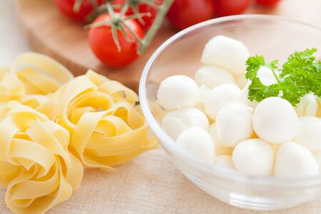 uncooked pasta and mozzarella in a bowl, raw food photo