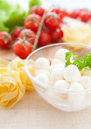 raw pasta in a bowl and mozzarella, cherry tomatoes, vertical photo