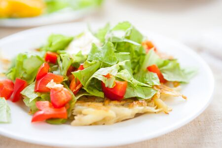 Potato pancakes with lettuce top, close up photo