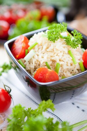 cooked brown rice and cherry tomatoes, close up photo