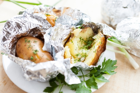delicious potatoes cooked in foil with herbs, close up