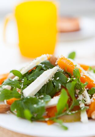 pumpkin salad with arugula and feta, closeup photo