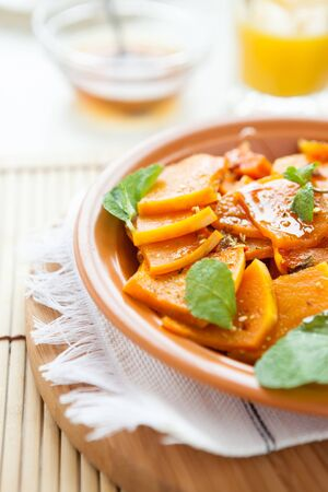 pumpkin cooked with honey and mint on a dish, closeup Stock Photo