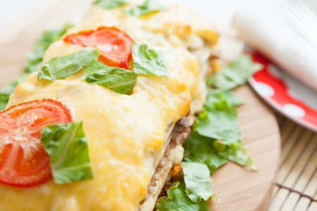 Vegetable lasagna with tomato on top, closeup photo