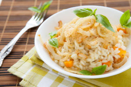 risotto with pumpkin and onion slices, closeup photo