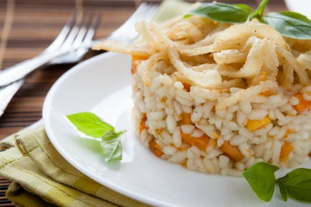 tasty vegetable risotto with onion and basil, closeup photo