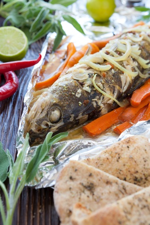 river fish with vegetables baked in foil, closeup photo