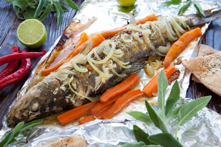 zander: big zander baked with vegetables in foil, fish closeup Stock Photo