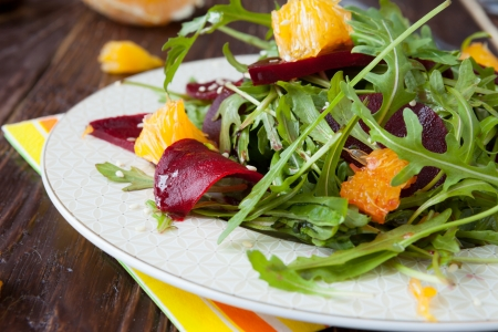 beet salad with arugula and slices of orange, closeup