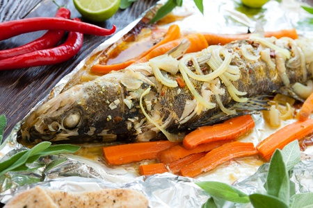 Baked fish with carrots and onions in foil, closeup Stock Photo - 18847412