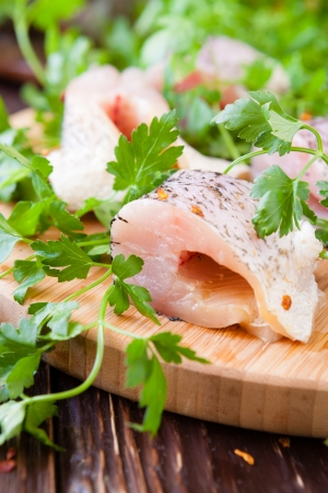 pike fillet pieces on a cutting board and a sprig of parsley, closeup Stock Photo - 19157557