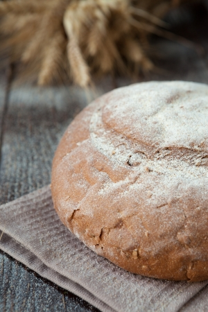 round loaf of bread and wheat ears, closeup photo