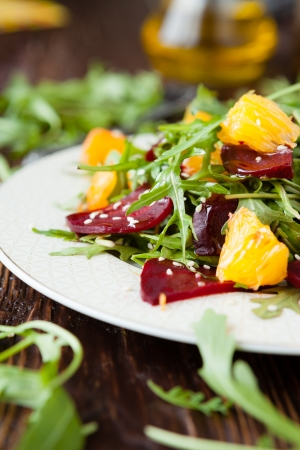 green salad: fresh salad with arugula and citrus, healthy food closeup