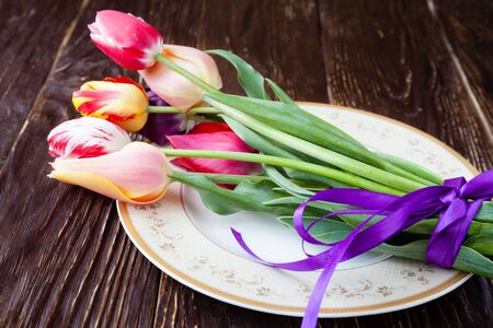 armful: armful of tulips on a plate, close up flowers