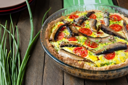 Homemade quiche with vegetables and fish, sprats, food closeup
