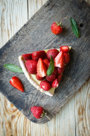 piece of tart with custard and strawberries, top photo