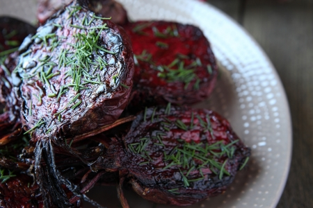 roasted halves of young beets with herbs, food close up