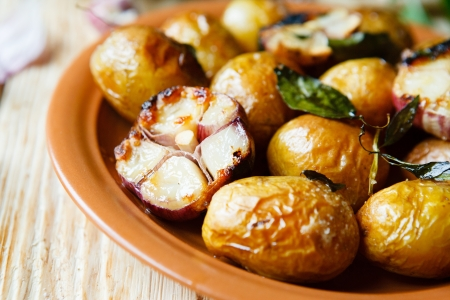 Potatoes roasted in their jackets with garlic, food close up