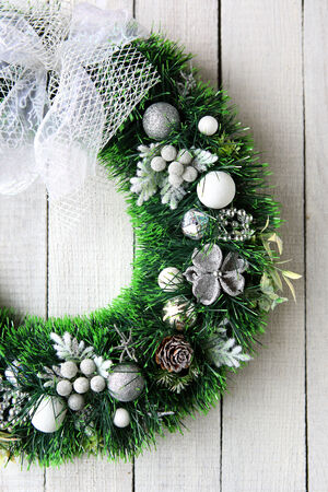 Christmas wreath in silver on white door, food close up