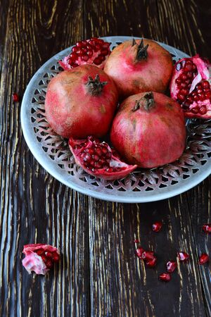 lots of ripe pomegranate in a beautiful bowl, food closeup photo