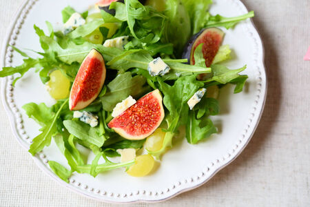 salad with figs, cheese and grapes, top view, food photo