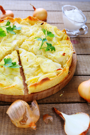 Round flan with onions, quiche, food closeup