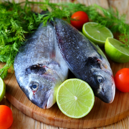 daurade: two uncooked fish dorado on board, food closeup Stock Photo