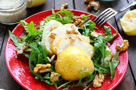 salad of arugula with pear and lemon sauce, food closeup Stock Photo