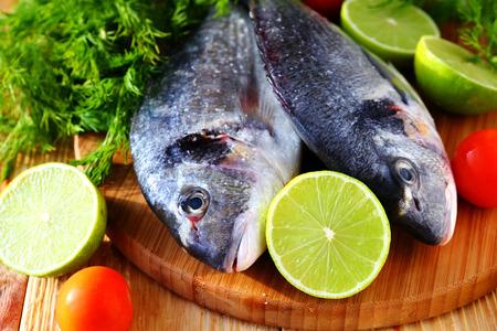 daurade: raw fish, lime and herbs, cooking closeup Stock Photo