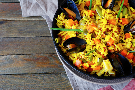Vegetable paella with seafood, top view, food closeup photo