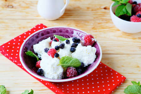 cottage cheese with fresh raspberries and blueberries, food closeup photo