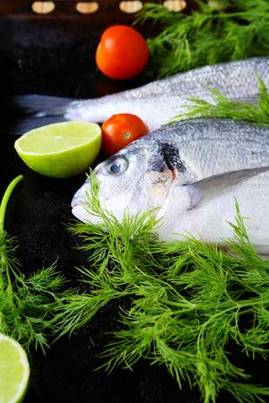 daurade: fresh fish on a baking sheet and greens, food closeup Stock Photo
