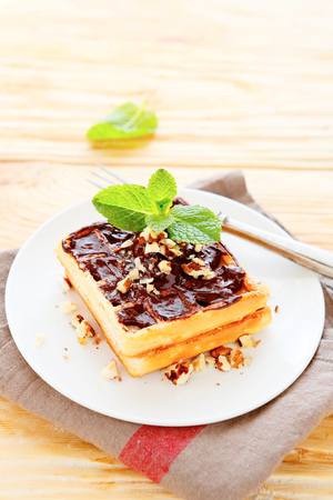 bord eten: light waffles with chocolate on a white plate, food closeup Stockfoto