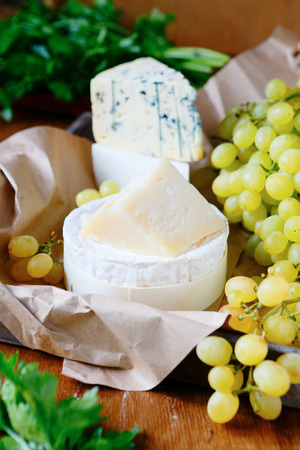 goat cheese, parmesan, brie and Camembert with Grapes, food closeup photo