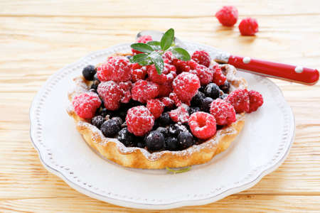 tartlet with fresh raspberries and currants, food closeup photo