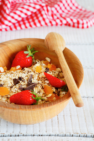 granola with strawberries and chocolate chips, food closeup photo