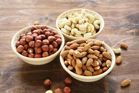 nuts in bowls, cashews, almonds and hazelnuts, food 스톡 콘텐츠