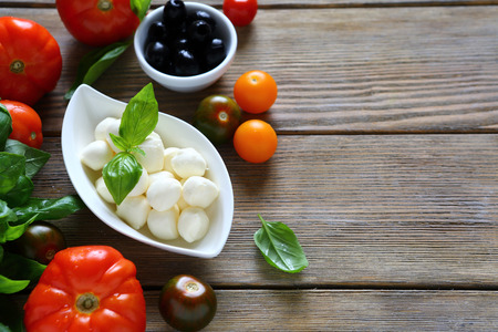 mozzarella balls and other foods on wooden background photo