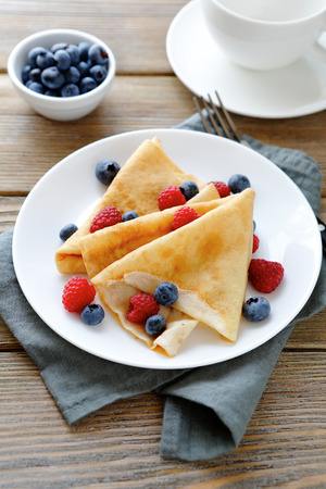 delicious pancakes, crepes with raspberries and blueberries, food closeup