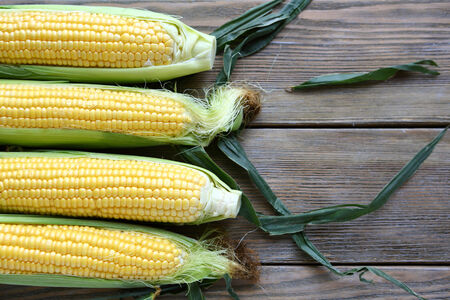 corn on the cob: corn cob and green leaves on wooden background, food Stock Photo