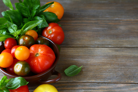 wooden background with tomatoes and basil, food closeup photo