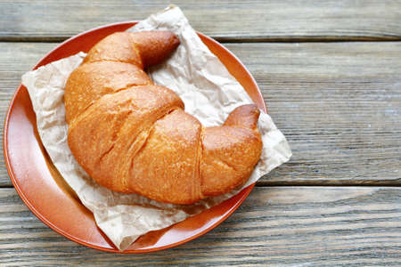 plate of food: One croissant on a plate, food closeup