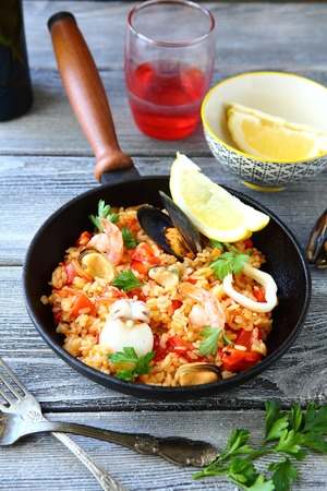 Tasty paella mussels and squid with black tiger prawns, top view