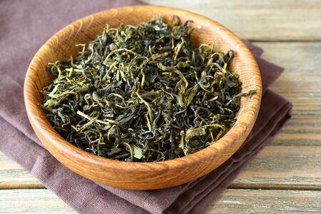 green tea leaves: Green Tea leaves in a bowl, fragrant tea Stock Photo