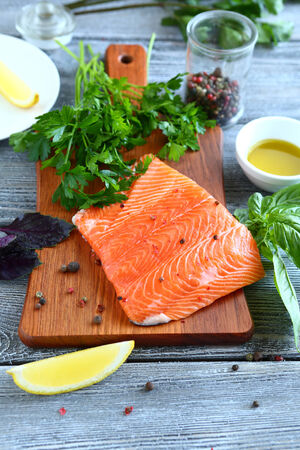 Salmon steak with lemon on a cutting board, tasty food photo