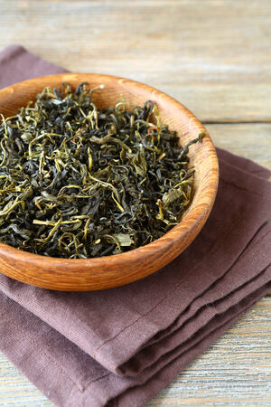 green tea leaves: Tea in a wooden bowl, closeup