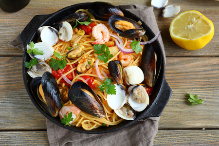 Tasty pasta with mussels, squid, parsley and lemon, top view
